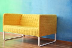 Stylish sofa near color wall Royalty Free Stock Images