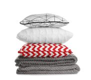 Stylish soft pillows and folded plaids on white. Background stock photos