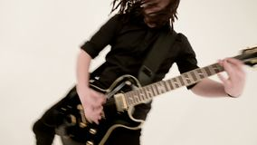 Stylish solo guitarist with dreadlocks on his head and in black clothes on a white background expressively playing the stock video footage