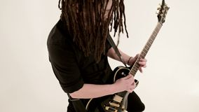 Stylish solo guitarist with dreadlocks on his head and in black clothes on a white background expressively playing the stock footage