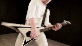 Stylish solo guitarist with dreadlocks on his head and in white clothes on a black background expressively playing the stock footage