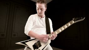 Stylish solo guitarist with dreadlocks on his head and in white clothes on a black background expressively playing the stock video