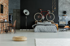 Stylish spacious bedroom. Stylish designed spacious bedroom with red bike above the bed Royalty Free Stock Images