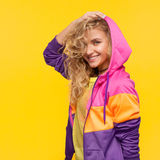 Stylish sportive girl on orange. Young curly woman in colorful sportive clothing posing happily on orange background Stock Photography
