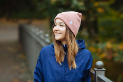 Stylish sporty brunette woman close up in trendy urban outwear posing at bridge forest city park on cold rainy fall day. Vintage f Royalty Free Stock Photo