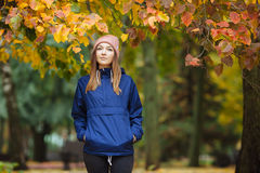 Stylish sporty brunette woman close up in trendy urban outwear posing at bridge forest city park on with golden yellow foliage. Vi Royalty Free Stock Photo