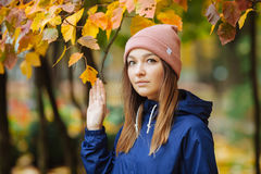 Stylish sporty brunette woman close up in trendy urban outwear posing at bridge forest city park on with golden yellow foliage. Vi Stock Photography