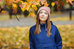 Stylish sporty brunette woman close up in trendy urban outwear posing at bridge forest city park on with golden yellow foliage. Vi Stock Image