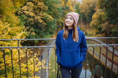 Stylish sporty brunette woman hands in pockets in trendy urban outwear posing at bridge forest city park on cold rainy fall day. V Royalty Free Stock Photo