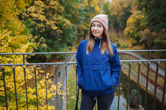 Stylish sporty brunette woman hands in pockets in trendy urban outwear posing at bridge forest city park on cold rainy fall day. V Royalty Free Stock Photos
