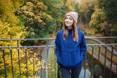 Stylish sporty brunette woman hands in pockets in trendy urban outwear posing at bridge forest city park on cold rainy fall day. V Royalty Free Stock Image