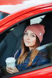 Stylish sporty brunette woman in trendy urban outwear driving a car with big white disposable cup straw cold fall day Vintage filt Stock Image