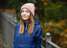 Stylish sporty brunette woman in trendy urban outwear posing at bridge forest city park on cold rainy fall day. Vintage filter fil Stock Photo