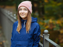 Stylish sporty brunette woman in trendy urban outwear posing at bridge forest city park on cold rainy fall day. Vintage filter fil Royalty Free Stock Images