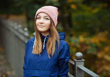 Stylish sporty brunette woman in trendy urban outwear posing at bridge forest city park on cold rainy fall day. Vintage filter fil Stock Image