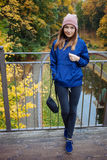Stylish sporty brunette woman in trendy urban outwear posing at bridge forest city park on cold rainy fall day. Vintage filter fil Royalty Free Stock Photos