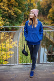 Stylish sporty brunette woman in trendy urban outwear posing at bridge forest city park on cold rainy fall day. Vintage filter fil Royalty Free Stock Image