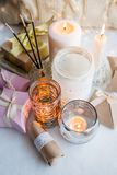 Stylish still life with gift boxes, candle sticks, burning candles, garland on light windowsill background, boho romance concept. Background and style stock photos