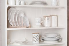 Stylish storage stand with different ceramic dishware. At home royalty free stock photography