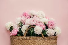 Stylish straw rustic bag with white and pink peonies on pastel pink paper, flat lay with copy space. Hello spring concept. International Women`s Day. Happy stock photography