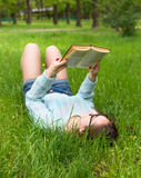 Stylish student girl relax with book in beautiful summer park at sunny day. Outdoor lifestyle picture Royalty Free Stock Photos