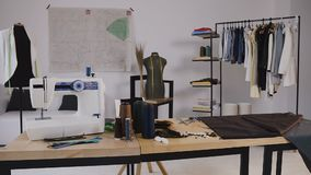 A stylish studio for sewing clothes which has it sewing machine, coil threads, various sewing Items and fabrics laying. Around, mannequins standing and Sketches stock video