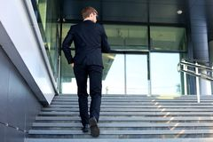 Stylish successful businessman goes up the stairs of the office building stock images