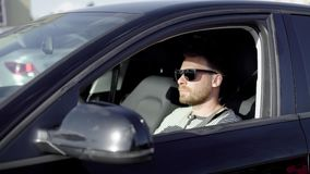 Stylish successful man driving a black luxury car in summer. stock video footage