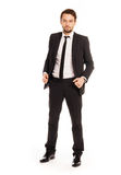 Stylish successful young businessman. Standing looking confidently at the camera with an unbuttoned suit jacket, full length on white Stock Photography