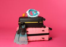 Stylish suitcases with swimming mask and flippers. On color background stock images