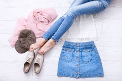 Stylish summer outfit with different accessories and female legs in jeans on white wooden floor. Top view and copy space. royalty free stock image