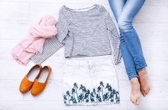 Stylish summer outfit with different accessories and female legs in jeans on white wooden floor. Top view and copy space. royalty free stock photography