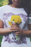 Stylish tanned girl holding bunch of yellow dandelions in her hands Royalty Free Stock Image