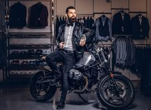 Stylish tattooed bearded man with dressed in black leather jacket and bow tie posing near retro sports motorbike at men. Stylish tattooed bearded man with stock images
