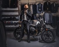 Stylish tattooed bearded man with dressed in black leather jacket and bow tie posing near retro sports motorbike at men. Stylish tattooed bearded man with royalty free stock image