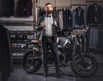 Stylish tattooed bearded man with dressed in black leather jacket and bow tie posing near retro sports motorbike at men royalty free stock images