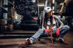 Stylish tattooed girl holding a big wrench sitting on a hydraulic hoist with a suspended car engine in the workshop. Stylish tattooed girl holding a big wrench stock image