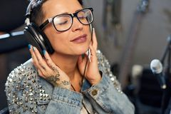 Content woman enjoying music in studio royalty free stock photography