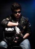 Stylish teen biker portrait. Nice boy wearing fashion leather jacket and sunglasses holding in hands helmet over dark blue background Stock Image