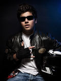 Stylish teen biker. Portrait, nice boy wearing fashion leather jacket and sunglasses holding in hands helmet over dark blue background Royalty Free Stock Photo
