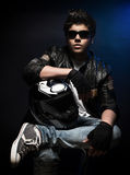 Stylish teen boy biker. Sitting and posing in the studio over dark blue background with helmet in hands, fashion for motorcyclist Royalty Free Stock Image