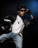 Stylish teen boy biker. Sitting and posing in the studio over dark blue background with helmet in hands, fashion for motorcyclist Stock Images