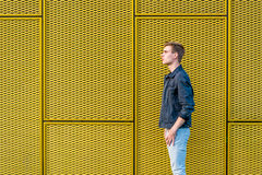 Stylish teen boy over industrial yellow background side view Stock Photo