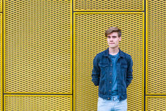 Stylish teen boy over industrial yellow background thinking Royalty Free Stock Image