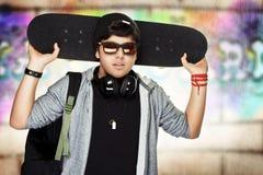 Stylish teen boy with skateboard Stock Photography