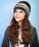 Stylish teen model. Portrait of nice stylish teen model wearing warm hat and posing over blue background, dreamy looking in side, winter fashion for girls Stock Photo