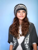Stylish teen model. Portrait of nice stylish teen model wearing warm hat and sweater, posing over blue background, dreamy looking in side, winter fashion for Stock Photography
