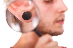 Teen boy with piercing and fashionable hairstyle. Stylish teenage boy close face profile, pierced ear black plug through the magnifying glass, isolated on white Royalty Free Stock Photo