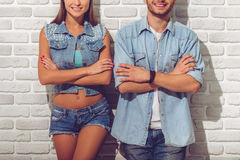 Stylish teenage couple. Cropped image of stylish teenage couple in jean clothes smiling while standing with crossed arms on white brick wall background Royalty Free Stock Photo