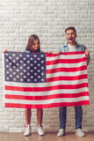 Stylish teenage couple. Full length portrait of stylish teenage couple holding American flag, looking at camera and smiling, on white brick wall background Royalty Free Stock Photos